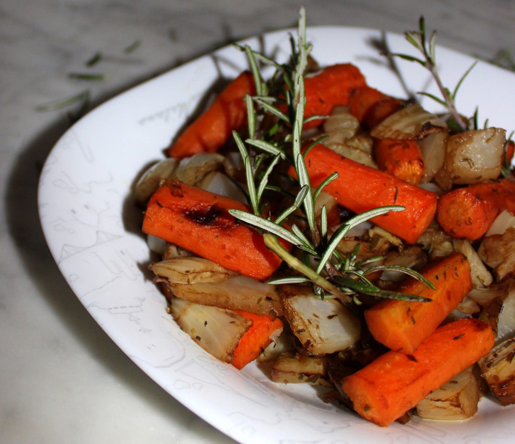 Plate of caramelized oven-roasted vegetables with a piece of rosemary
