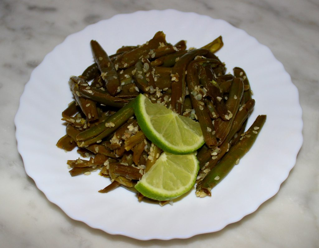 A plate of quick and easy exotic green beans with lime slices on top