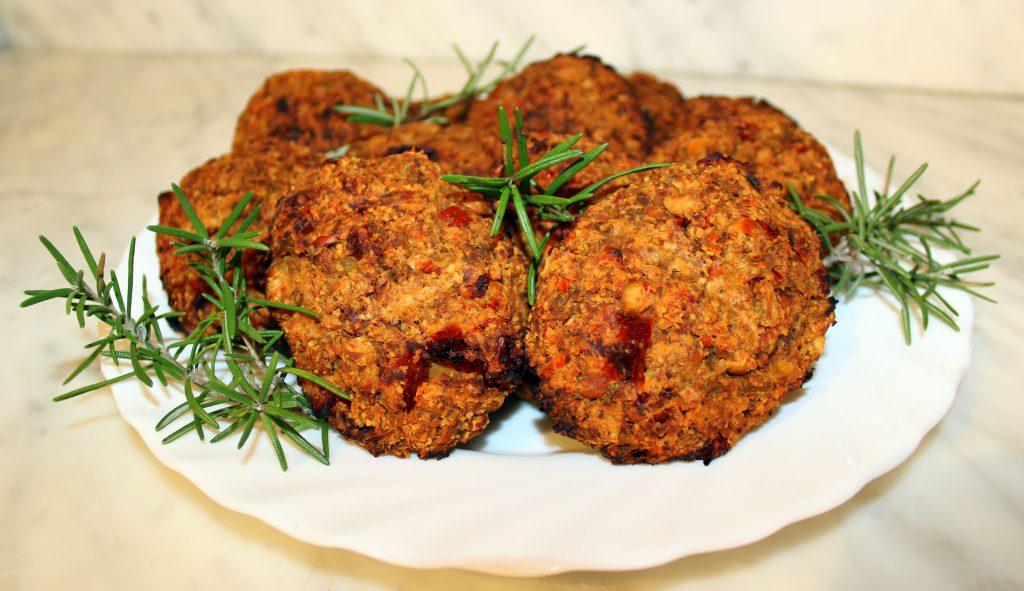 Eggplant and sundried tomato vegan burger patties on a plate with rosemary
