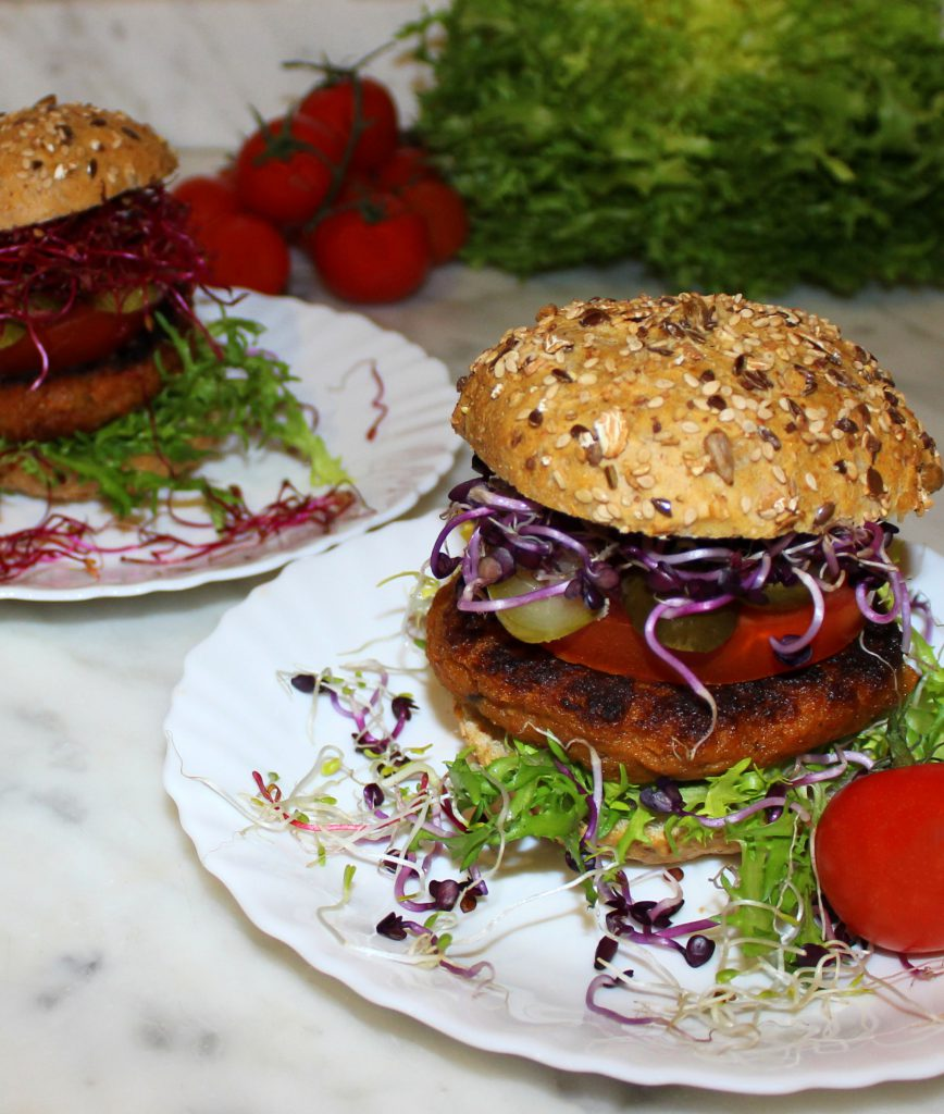 Eggplant and sundried tomato vegan burger in a bun with vegetables and purple sprouts