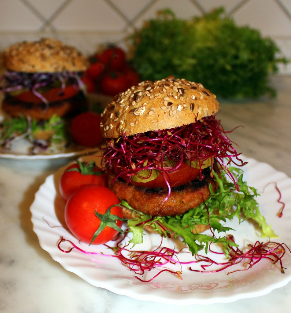 Eggplant and sundried tomato vegan burger in a bun with vegetables and pink sprouts