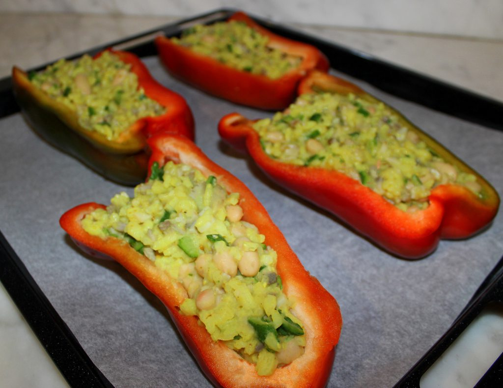 Four stuffed red bell pepper halves with zucchini and mushrooms uncooked