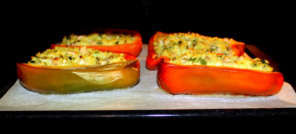 Four stuffed red bell pepper halves with zucchini and mushrooms cooking in the oven