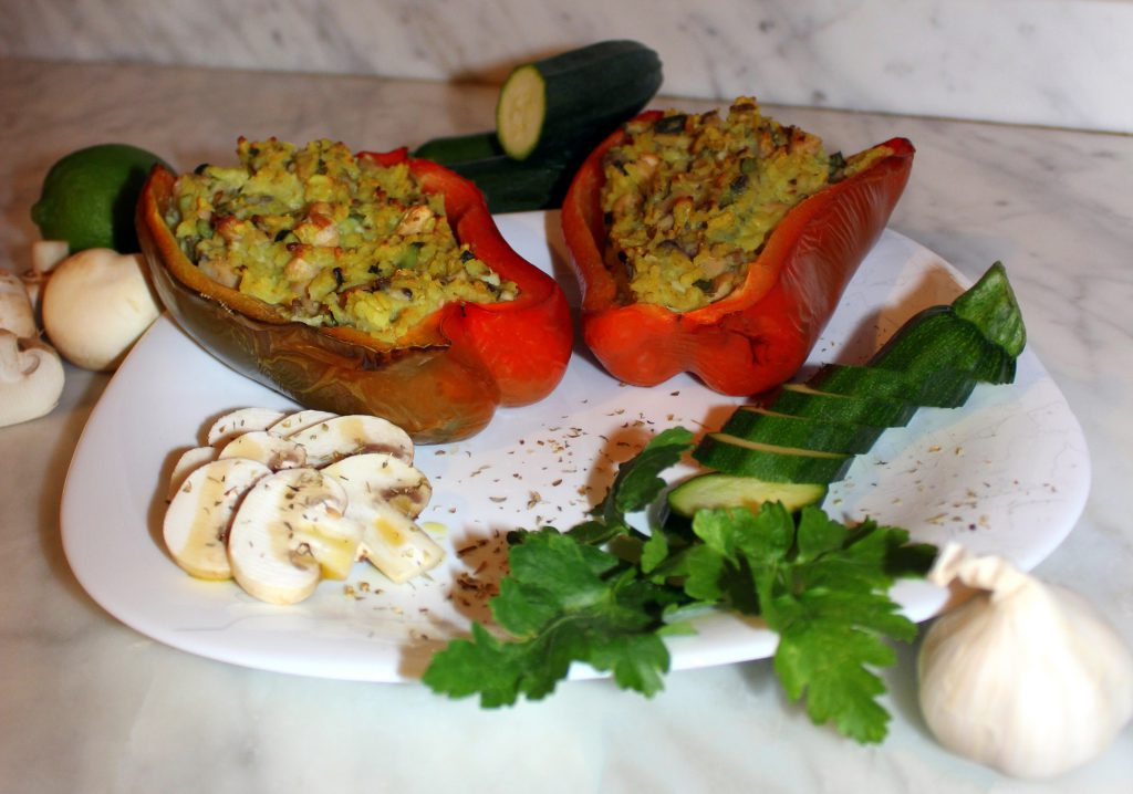 Two stuffed red bell pepper halves with zucchini and mushrooms
