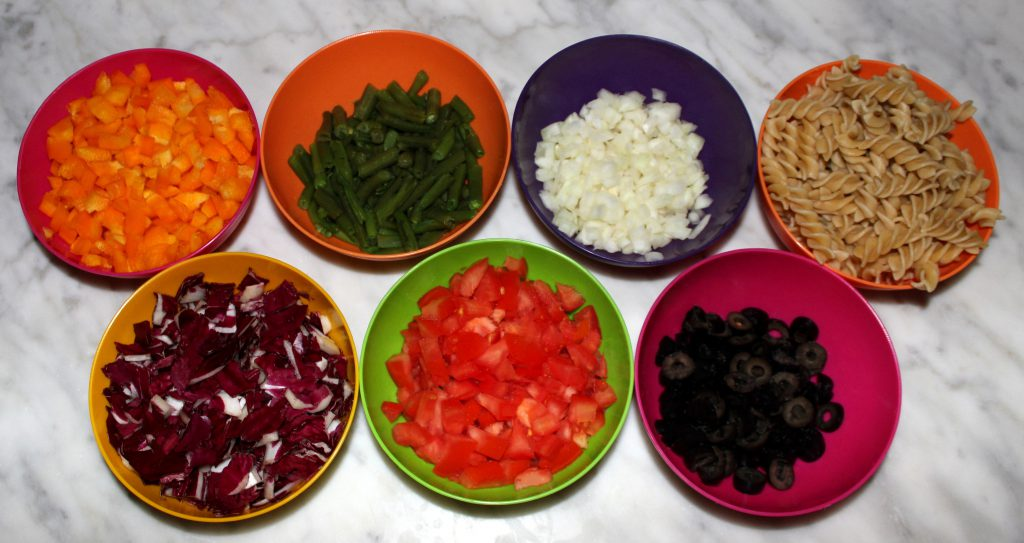 All seven ingredients of rainbow pasta salad in separate containers