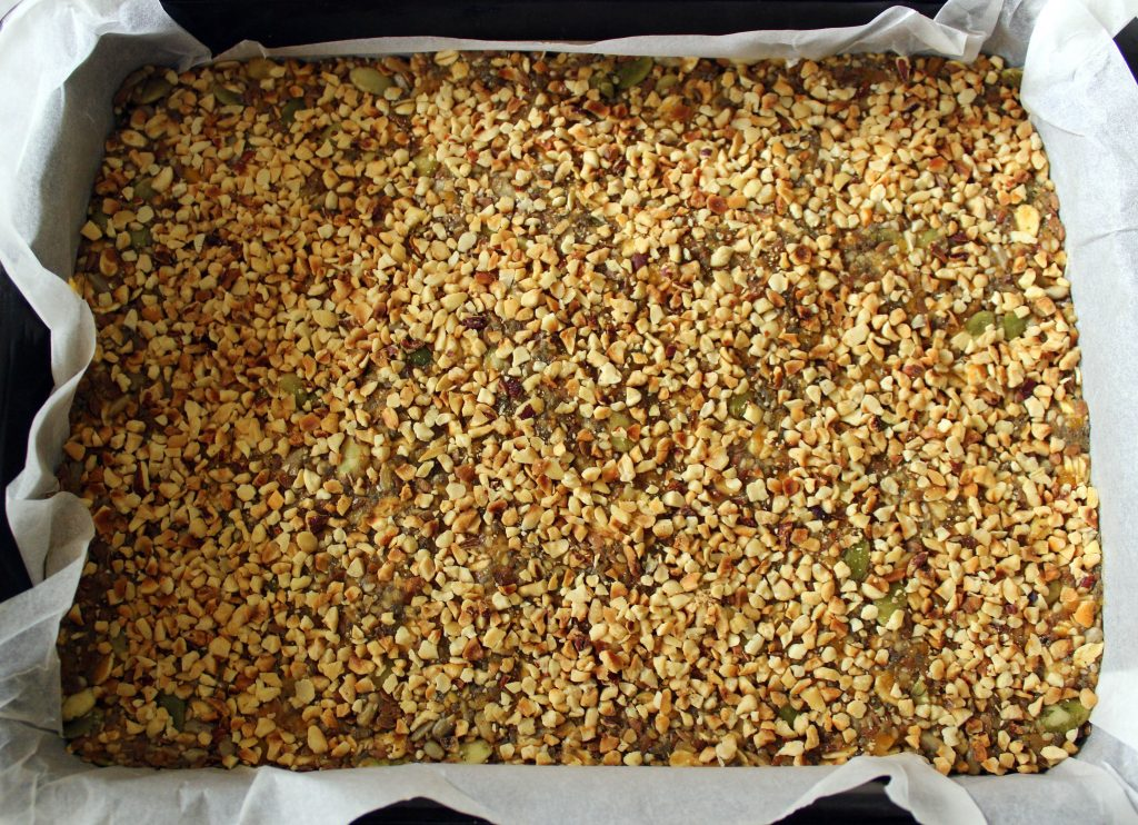 Mixture for healthy vegan no-bake protein bars before cooling covered with hazelnuts