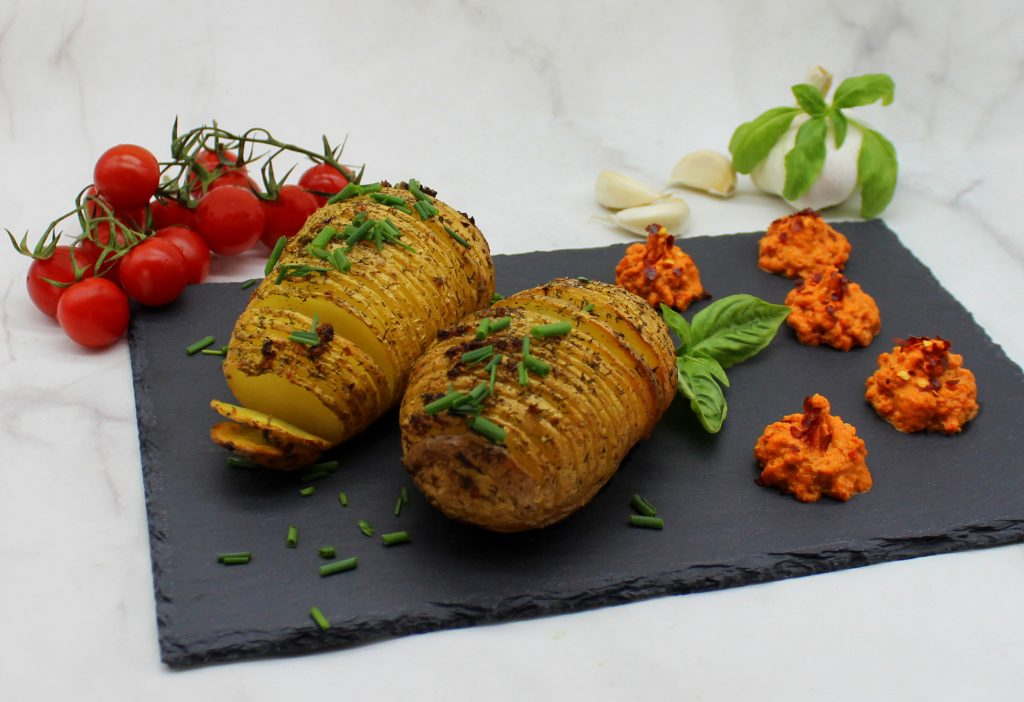 Crispy garlic Hasselback potatoes with spicy roasted bell pepper dip and chives on top