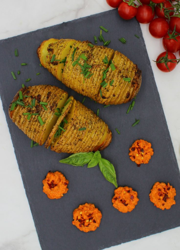 Potatoes with spicy roasted bell pepper dip and chives on top