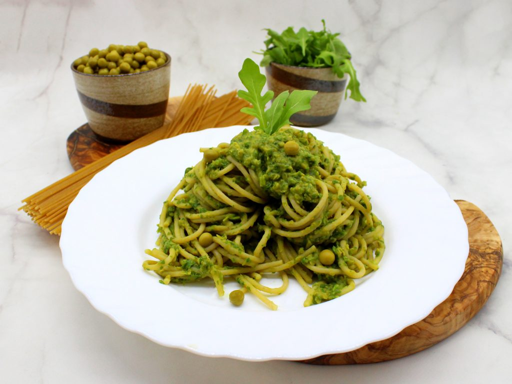 Dish of spaghetti with green pea and arugula sauce