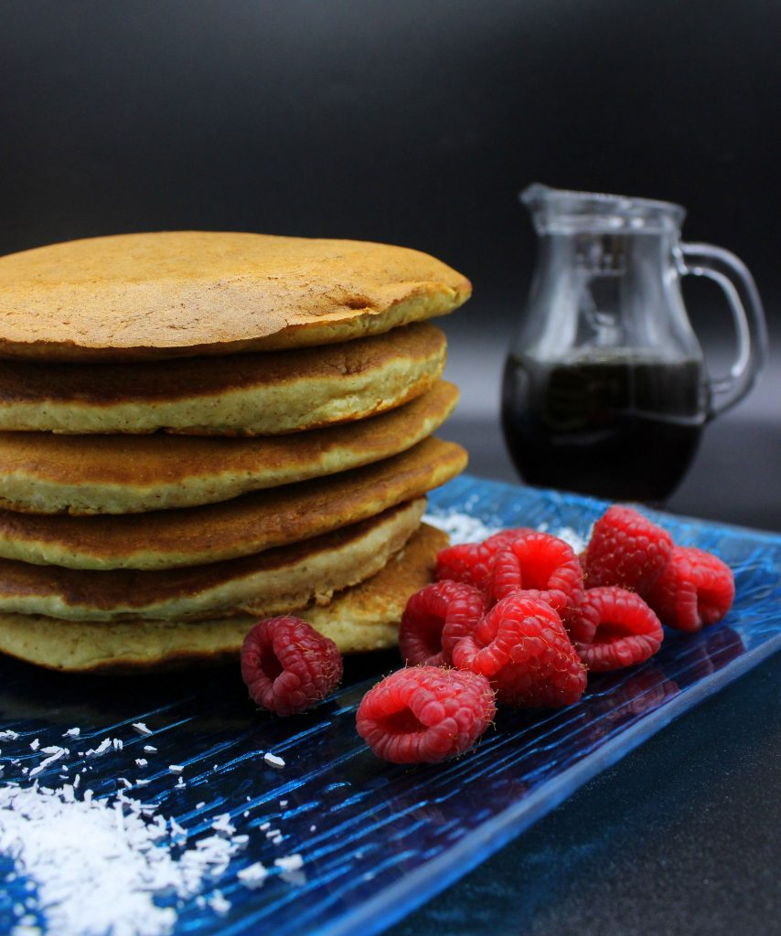 Vegan pancakes with raspberries and maple syrup on the side
