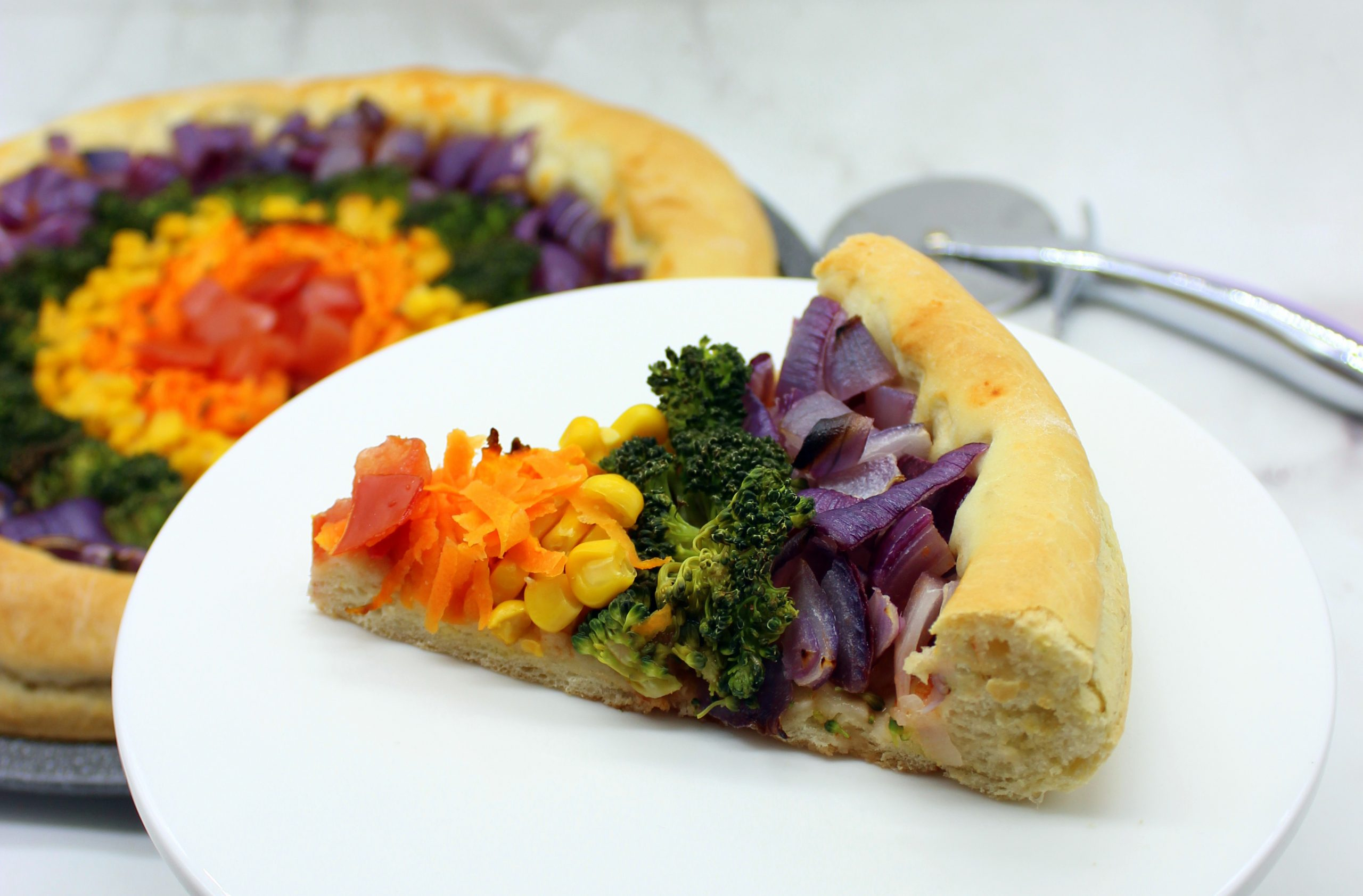 A slice of easy vegan rainbow pizza