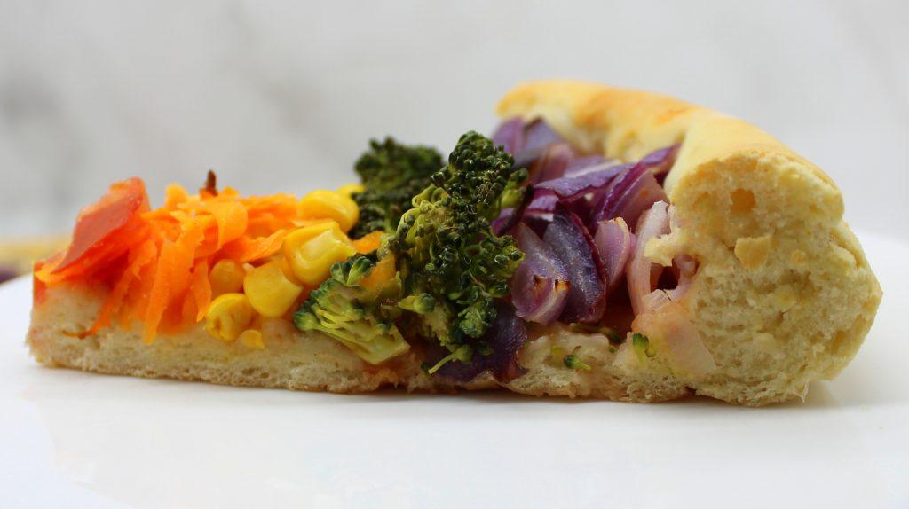 A slice of vegan rainbow pizza